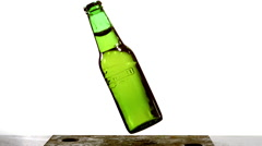 Bottle of Beer falling, Breaking and Splashing on Steel Plate against White Stock Footage