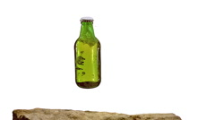 Bottle of Beer falling and Splashing on Stone against White Background, Slow Stock Footage