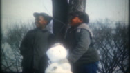 African American boys build snowmen on winter day, 3632 vintage film home movie Stock Footage