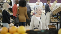 4K Friendly worker in a supermarket assisting senior lady buying groceries Stock Footage