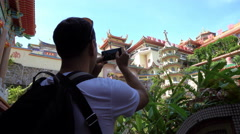 Caucasian man taking photo of Chinese temple Stock Footage