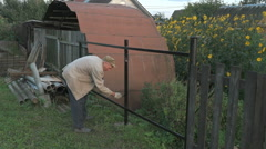 Old man 70s paints the iron fence using a black Stock Footage