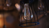 Focusing view of unlighted bulb hanging on ceiling Stock Footage