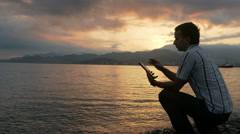 A man in a shirt checks messages on the tablet during the sunrise on the beach Stock Footage