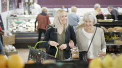 4K Senior lady & her adult granddaughter buying groceries in the supermarket Stock Footage