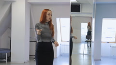 Ginger woman in striped blouse stands in middle of dancing room Stock Footage