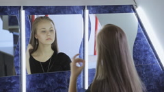 Pretty girl brushes her hair by hand sitting in front of mirror Stock Footage