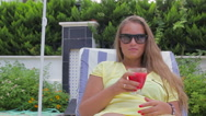 Beautiful girl drinking fruit juice while sitting by the pool Stock Footage