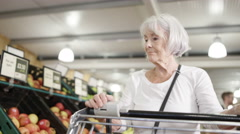 4K Senior lady with shopping cart buying groceries in the supermarket. Arkistovideo