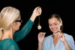 Hypnotherapist holding pendulum by patient against black background Stock Photos