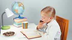 Schoolgirl reading a book in the evening and eating chocolate cookies Stock Footage
