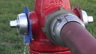 Red water hydrant on the street in use with fire hose attached Stock Footage