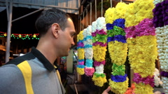 Caucasian man smelling Indian religous flower necklace at market stall Stock Footage