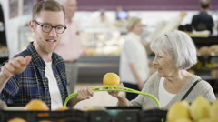 4K Senior lady & her adult grandson buying groceries in the supermarket Stock Footage