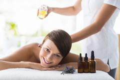 Portrait of smiling woman receiving massage treatment at spa Stock Photos