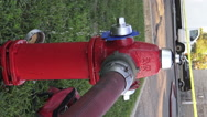 Red water hydrant on the street in use with fire hose attached (vertical footage Stock Footage
