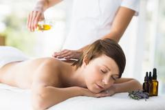 Relaxed woman receiving massage treatment at spa Stock Photos