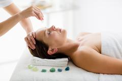 Masseur giving massage treatment to woman at spa Stock Photos