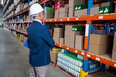 Business man is concentrating during his work in a warehouse Stock Photos