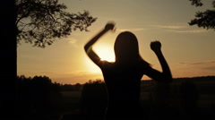 Young happy woman jumping, dancing and having fun in the forest at sunset Stock Footage