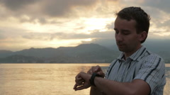A man in a shirt checks messages on smart watch during the sunrise on the beach Stock Footage