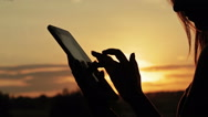 Female silhouette using a digital tablet in the forest at sunset Stock Footage