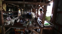 Girl in the textile production village weaving silk with loom in the house Stock Footage