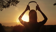 Woman putting on the headphones, listening to music and dancing in the forest Stock Footage
