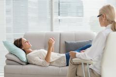 Woman talking to her therapist while lying on sofa at home Stock Photos