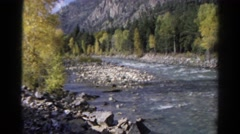 1967: train runs along the edge of river near wooded area. COLORADO Stock Footage