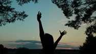 Happy young woman silhouette against sky lifts hands up in air Stock Footage