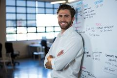Portrait of confident businessman leaning on whiteboard in office Stock Photos