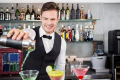 Waiter pouring cocktail into glasses at bar counter in restaurant Kuvituskuvat