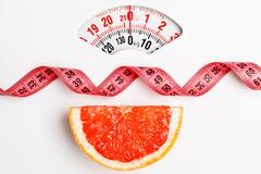 Grapefruit with measuring tape on weight scale. Dieting Stock Photos