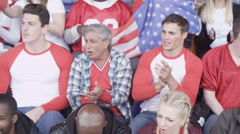 4K Crowd of spectators watching sports game in stadium waving to camera Stock Footage
