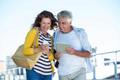 Happy couple using digital tablet and mobile phone on walkway in city Stock Photos