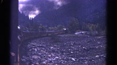 1967: the train makes it's was around the base of cold blue mountain. COLORADO Stock Footage