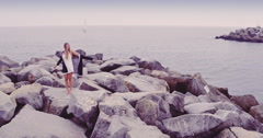 Aerial of beautiful woman dancing on rocks at harbour entrance in Santa Cruz Stock Footage