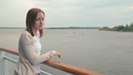 Young beautiful woman standing on deck of cruise ship and looking at river. Stock Footage