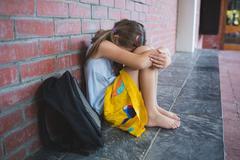 Sad schoolkid sitting alone in corridor at school Stock Photos