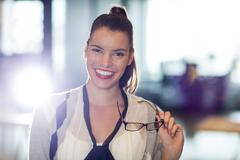 Portrait of smiling young woman holding eyeglass in office Stock Photos