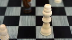 Black chess player knocks down the white king with his Knight Stock Footage