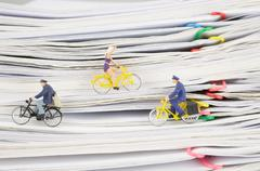 Close up postmen and woman cycling on pile overload paperwork Stock Photos