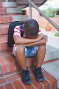 Sad schoolboy sitting alone on staircase at school Stock Photos