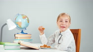 Portrait profile blonde school girl 7-8 years reading book eating candy Stock Footage