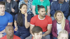 4K Sports fan sitting with supporters of the other team shows disappointment Stock Footage