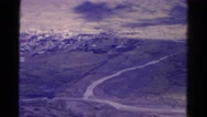 1967: curving and splitting road divides mountains and populated area COLORADO Stock Footage