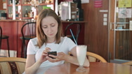Woman using smartphone in cafe Stock Footage