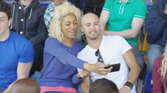 4K Couple sitting in the crowd at sports event pose to take a selfie with phone Stock Footage