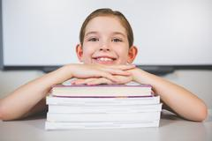 Portrait of smiling girl leaning on stack of books in class room at school Kuvituskuvat